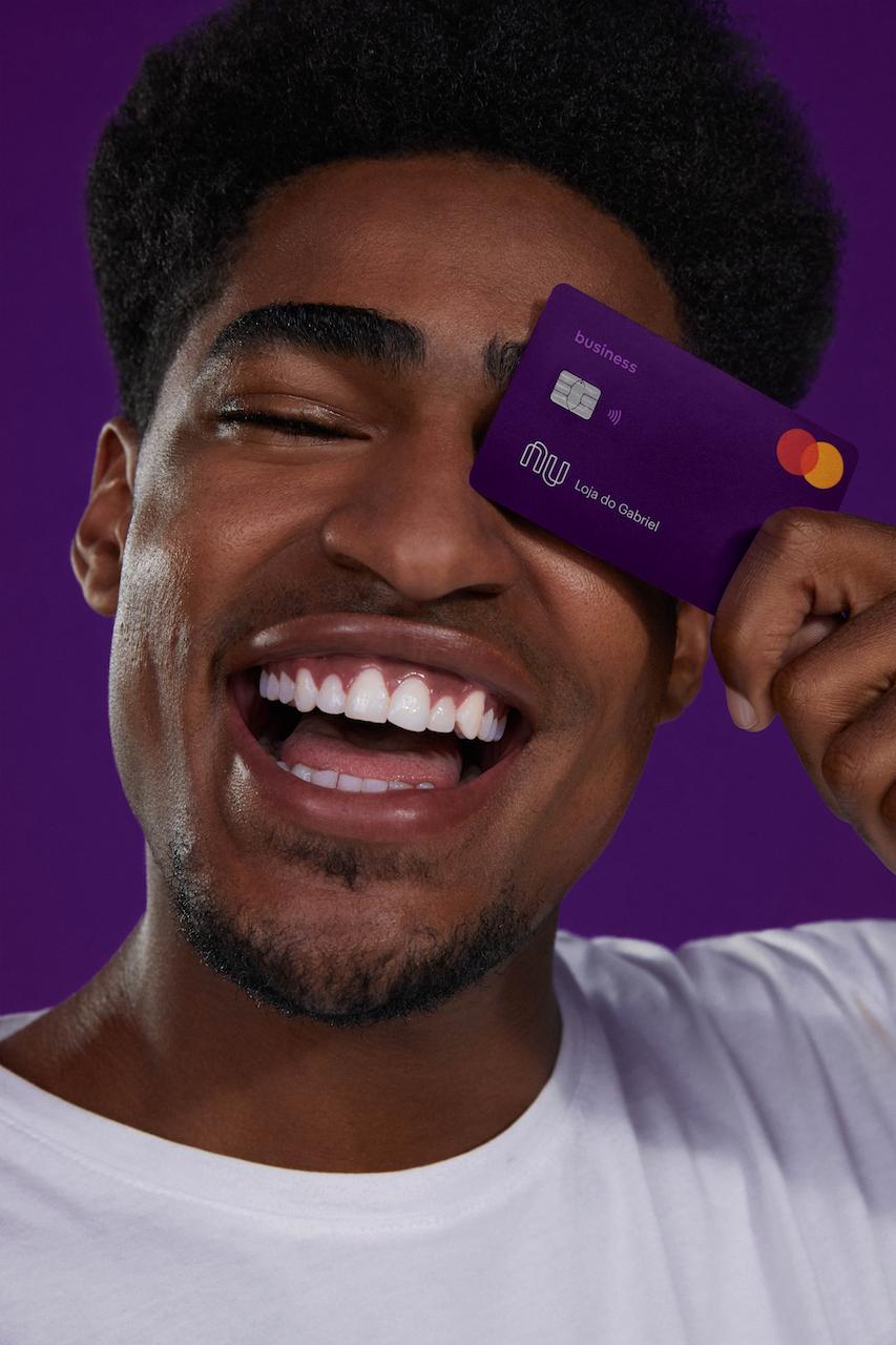 Cartão PJ: no fundo roxo, fotografia de um homem segurando o cartão PJ em frente ao olho esquerdo