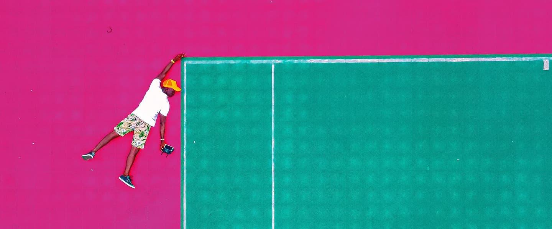 Como funciona o MEI: no fundo rosa, ilustração de um homem se segurando na ponta de uma quadra de tênis
