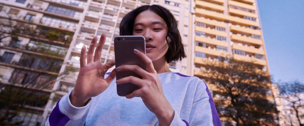 Chaves Pix no Nubank: mulher asiática segurando um celular em frente a um prédio