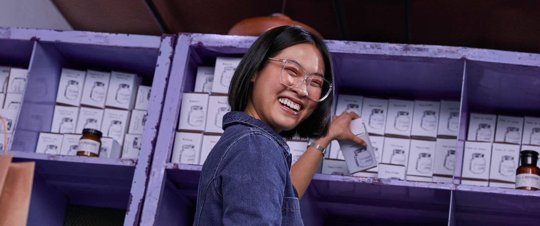 uma mulher tirando um pote de uma prateleira