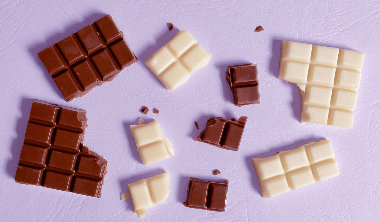 Drawback: Foto de vários quadradinhos de chocolate branco e ao leite espalhados por um fundo lilás