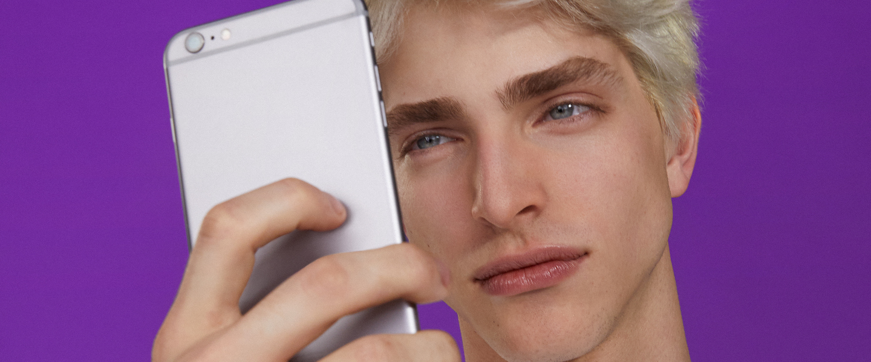 Notificações no app Nubank: em foto de estúdio com fundo roxo, um homem olha para a tela do celular que ele segura em frente ao rosto.