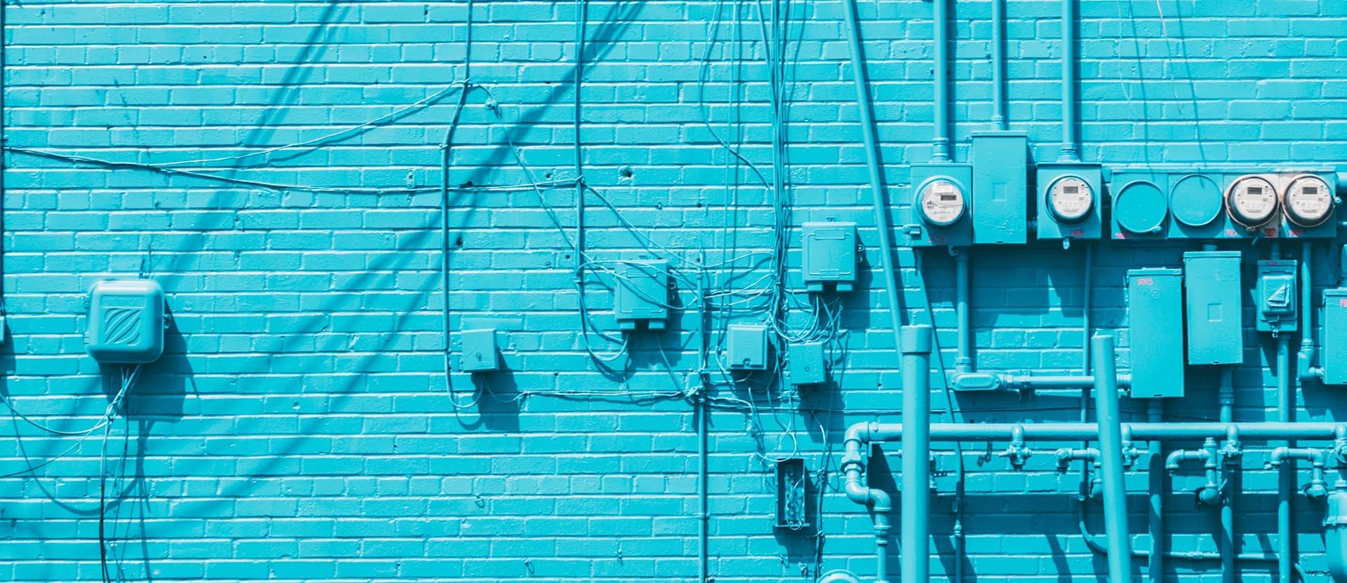 imagem de uma parede azul clara cheia de fios elétricos e disjuntores
