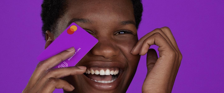 Vencedor Prêmio Reclame Aqui: foto mostra jovem com cartão de crédito nubank em frente ao rosto e sorrindo
