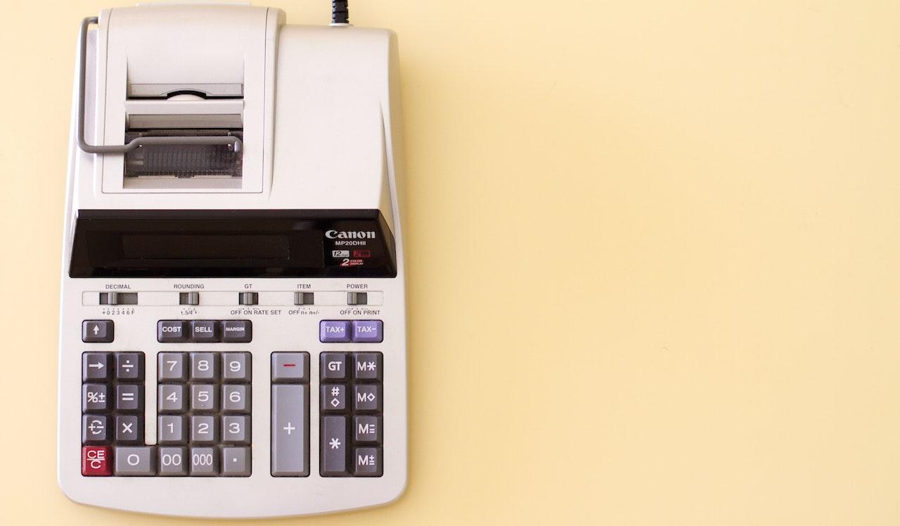 Imagem de uma calculadora analógica branca sobre um fundo amarelo claro