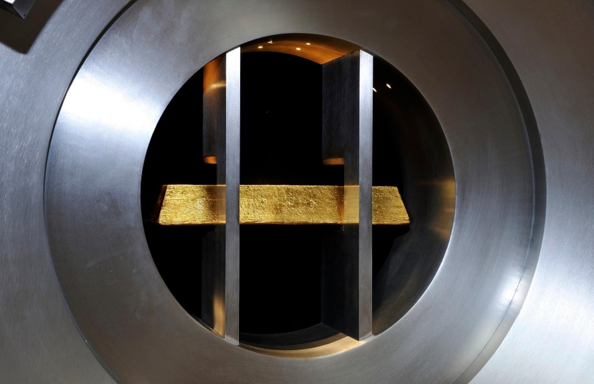 Foto da barra de ouro enquadrada pela porta da antiga casa forte.