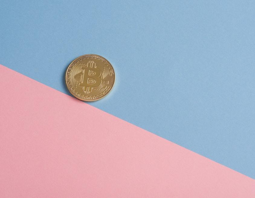 Bitcoin: uma moeda dourada de bitcoin sobre uma superfície azul e rosa