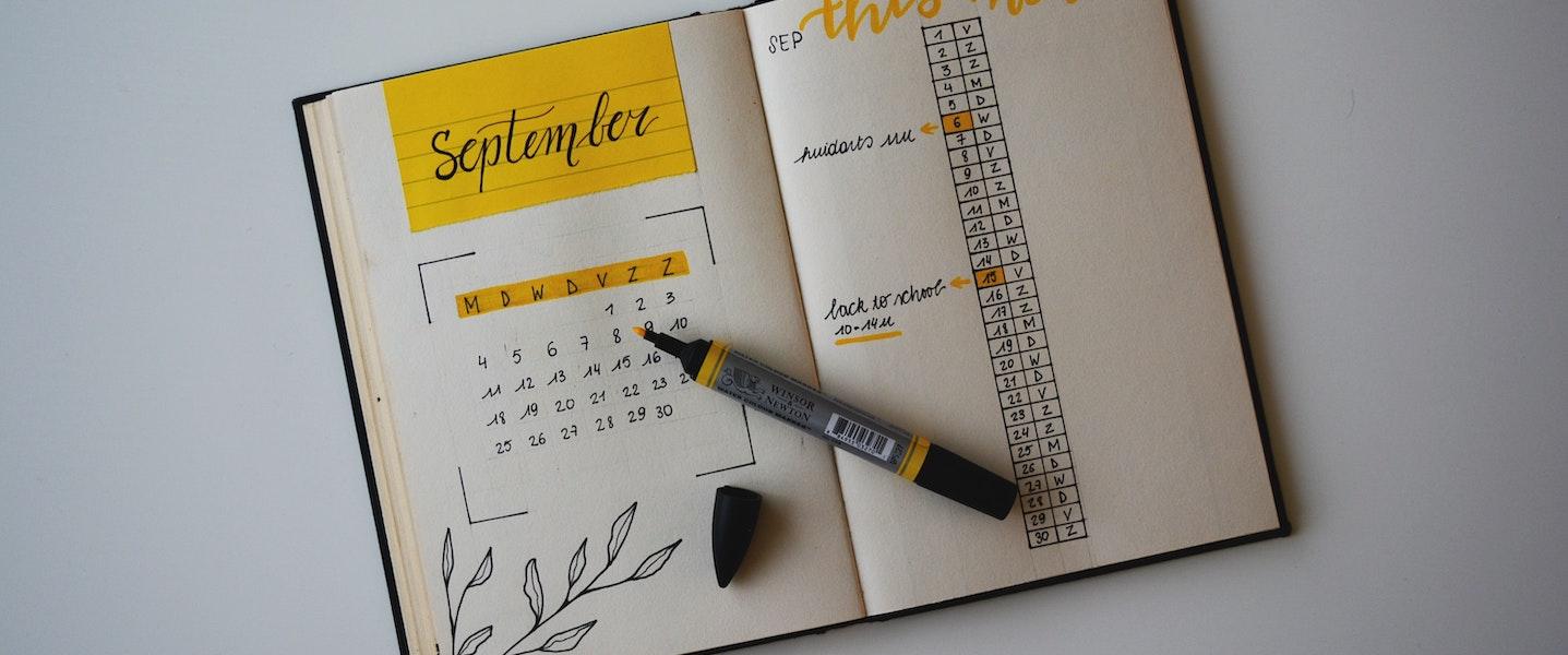 Uma agenda com um calendário desenhado com canetas preta e amarela