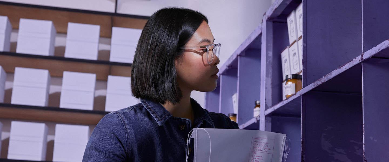 Conta PJ Nubank vale a pena: mulher de óculos e cabelo curto fazendo inventário em uma prateleira roxa