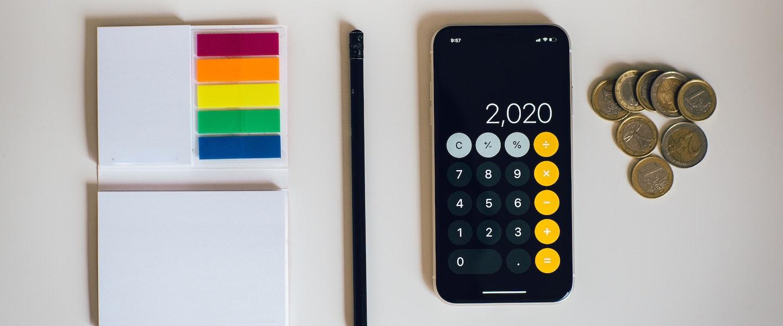 Contribuição MEI INSS 2021: fotografia de um bloco de papel e outro de marcadores coloridos, um lápis preto, um celular com o aplicativo da calculadora aberto com o número 2.020 e algumas moedas sobre uma mesa branca