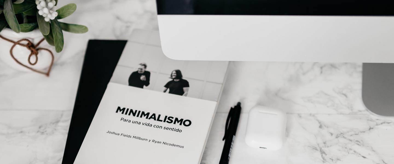 imagem minimalista, preta e branca, com imagem do livro em cuja capa está escrito minimalismo, caneta e partes de um computador