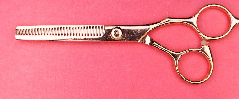 Imagem de uma tesoura dourada sem ponta em um fundo rosa