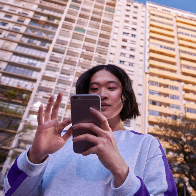 Foto mostra jovem de cabelos curtos mexendo no celular, com um prédio ao fundo
