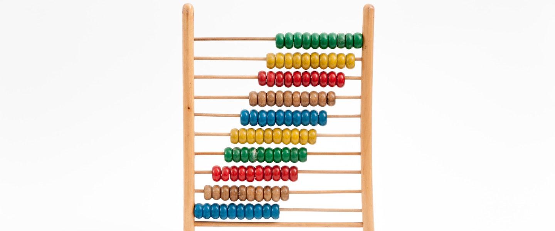 DAS MEI 2021: No fundo branco, fotografia de uma ferramenta de madeira com bolinhas coloridas para fazer contas matemáticas