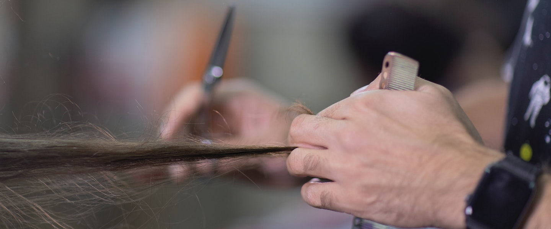Década do MEI: fotografia de uma pessoa cortando um cabelo cumprido. Uma mão segura o cabelo e outra segura a tesoura.