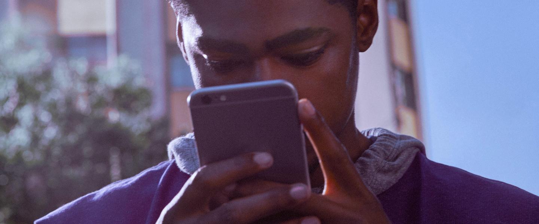 App Nubak login: jovem vestindo moletom roxo segura um celular em frente ao seu rosto enquanto sorri.