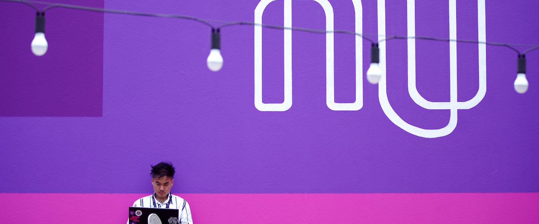 Garoto sentado em um tablado de madeira no canto esquerdo inferior da foto, segurando um notebook. Ele está em frente a um muro rosa e roxo onde está escrito NU em branco.