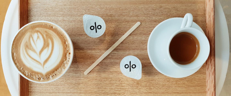 Quanto da renda devo destinar para investimentos: sobre uma mesa lateral branca, tem uma bandeja de madeira com uma xícara de café de um lado e uma de cappuccino no outro. Entre as xícaras, dois potinhos com símbolo de percentual e um palitinho de madeira entre eles
