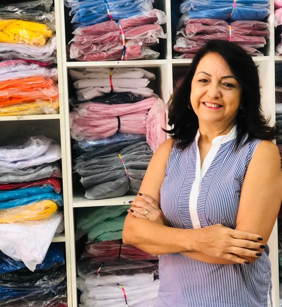 Silvia Veloso, proprietaria de confecção de braços cruzados na foto, blusa azul listrada e sorridente. Atrás dela existe um armário com peças da confecção dobradas e embaladas.