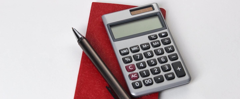 Tabela imposto de renda 2021: sobre uma mesa branca, repousam uma calculadora cinza e uma caneta preta sobre um caderninho vermelho