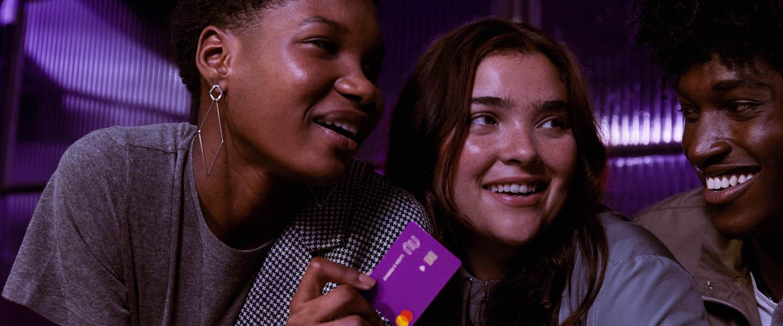 Imagem de duas mulheres e um homem sentados em um bar conversando. Uma das mulheres segura um cartão do Nubank.