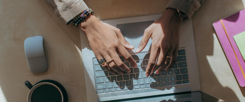 Imposto de Renda 2021 para MEI: fotografia de duas mãos digitando em um notebook apoiado numa mesa de madeira. Uma xícara preta de café e um mouse branco estão ao lado do computador.