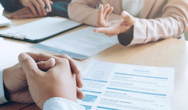 como fazer um currículo: currículo na mesa e duas pessoas que aparentam participar de uma entrevista de emprego