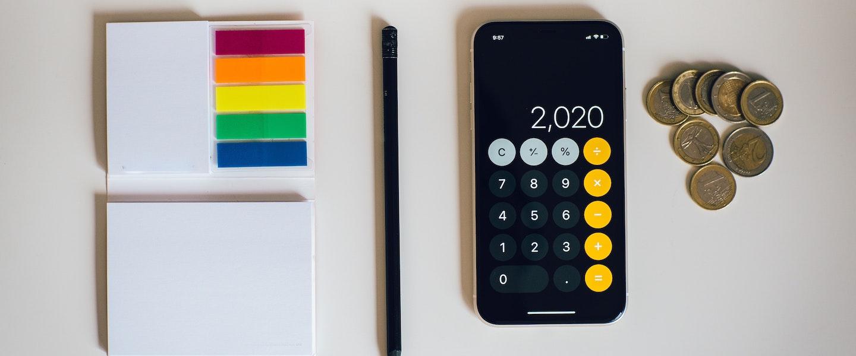 Fotografia de itens dispostos sobre uma mesa branca: um celular com a calculadora aberta, uma pilha de moedas, um lápis e um caderninho de anotações com post its coloridos
