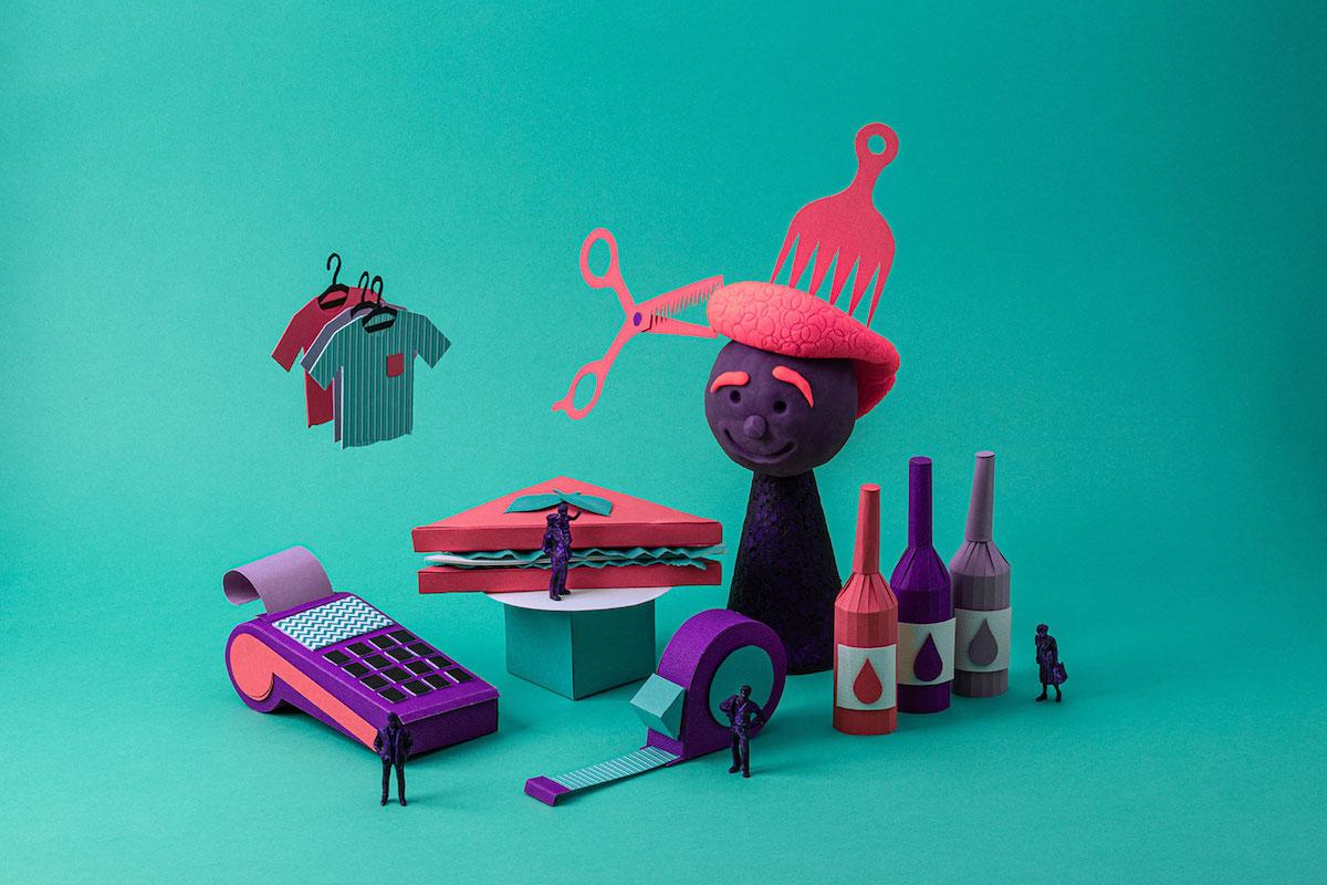 Data Nubank MEI: esculturas em papel de objetos do universo do MEI, como uma máquina de cartão, um hambúrguer, uma sacola e um tijolo. Pequenas figuras humanas de plástico também estão espalhadas.