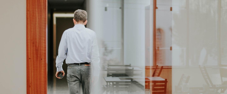 MP 1045 novo programa de suspensão de contrato e redução de jornada: fotografia de um homem de costas, com a carteira na mão, andando em direção oposta à câmera