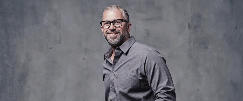 Foto de busto de Matt Swann, de óculos e camisa cinza em fundo cinza