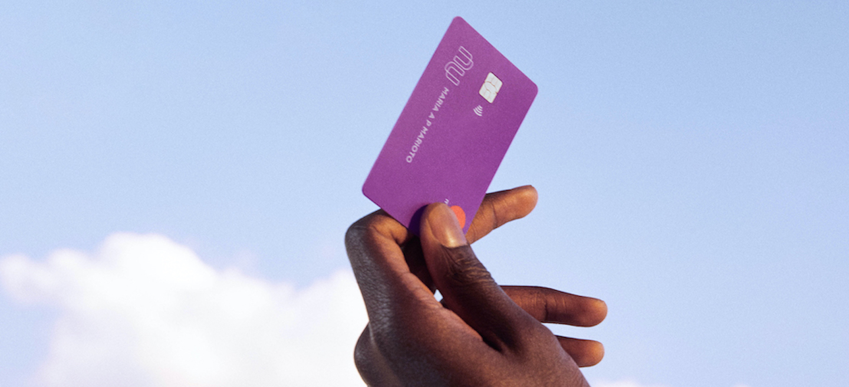 uma mão segurando um cartão Nubank apontado para o céu