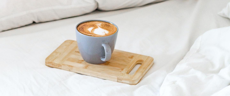 Pix funciona final de semana: fotografia de uma xícara de café cinza, com café dentro, sobre um suporte de madeira em cima de uma cama com lençol e travesseiros brancos