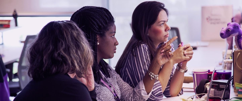 APM PROGRAM: Foto mostra três mulheres sentadas em frente a uma tela de computador, no escritório do Nubank