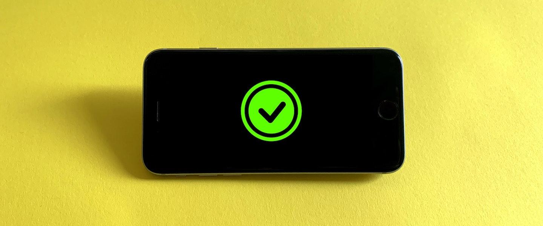 um celular com a tela com um símbolo de check em verde, em um fundo amarelo