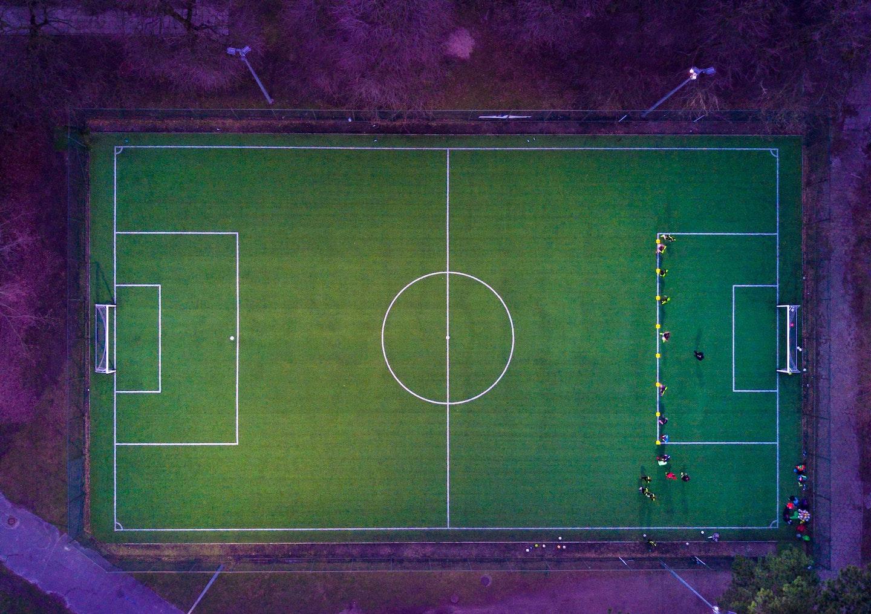 imagem de um campo de futebol com os arredores em tons de roxo