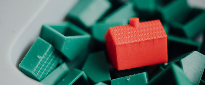 auxílio emergencial: casa vermelha feita de bloco de montar em cima de diversos blocos de montar verdes