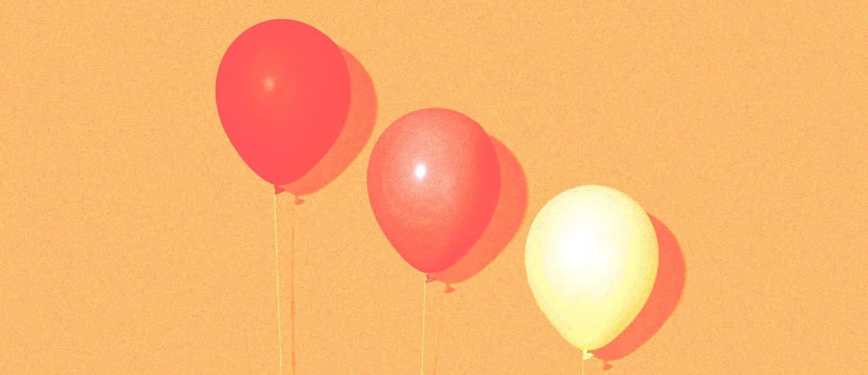dois balões laranjas e um balão amarelo, em um fundo laranja.