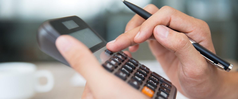 DARF: mulher faz algum tipo de cálculo segurando uma calculadora com a mão esquerda e uma caneta com a direita. Ao fundo é possível ver uma xícara da café e papeis.