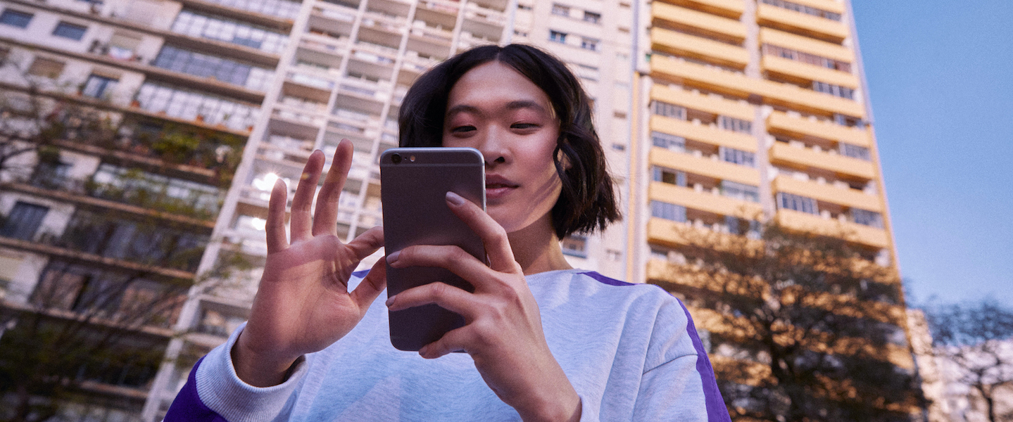 mulher segurando um celular em frente a um prédio