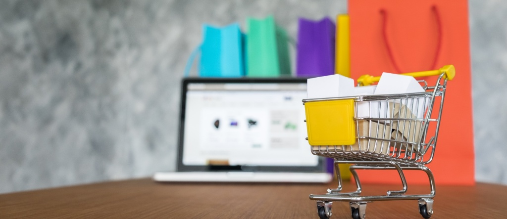 marketplace: imagem de um mini carrinho de supermercado cheio de sacolas dentro com um notebook ao fundo com uma loja online na tela e sacolas de compra em tamanho real atrás do notebook ilustrando compras em um marketplace online