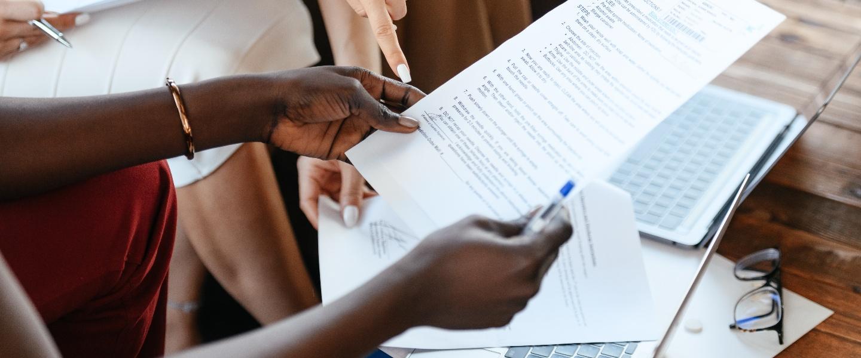 momento certo investimentos empresa: mulher negra empreendedora segurando um papel, caneta e apresentando o documento para outras pessoas