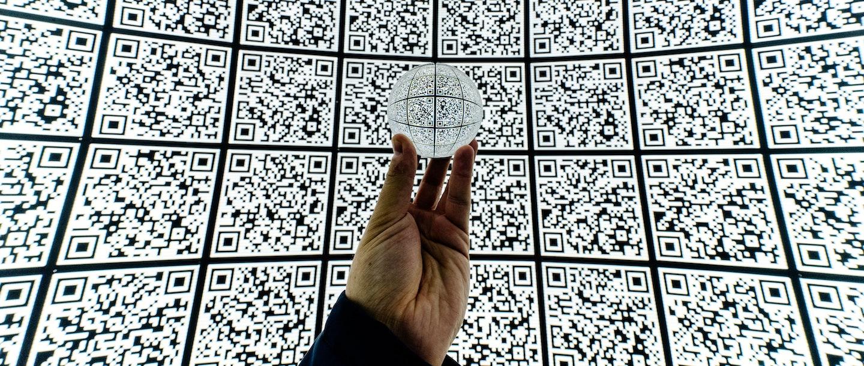 uma mão segurando um globo de QR Code em frente a um mural de QR Code