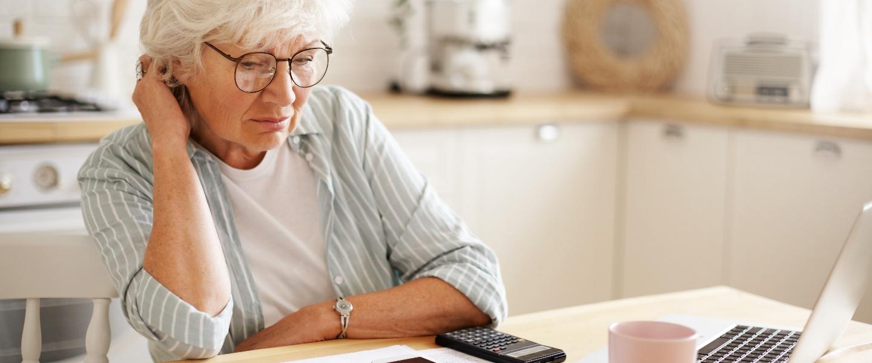 parar de contribuir inss: senhora idosa em frente ao computador fazendo cálculos com feição preocupada