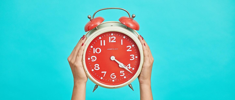 em um fundo verde claro, mãos segurando um relógio vermelho