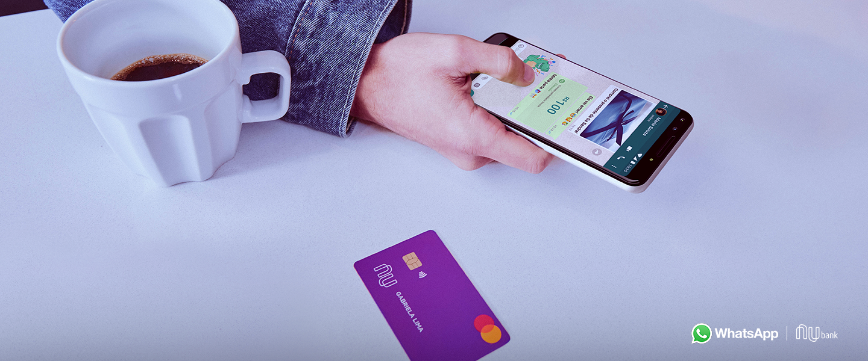 Pagamentos pelo WhatsApp: fotografia de um homem segurando o celular com o WhatsApp aberto fazendo um pagamento. Na bancada, uma xícara de café branca e o cartão Nubank do lado
