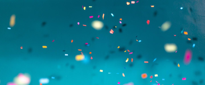 Saque-aniversário FGTS nascidos em maio: fotografia de confetes coloridos caindo num fundo azul (Crédito: Jason Leung)