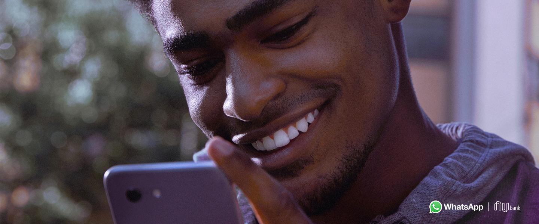 WhatsApp Pay Pagamentos: fotografia de um homem olhando para a tela do celular e sorrindo