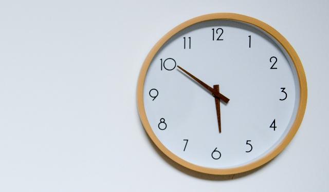 auxílio emergencial aniversariantes outubro: foto de relógio com moldura de madeira e fundo branco. Foto: Unsplash @Cast Coming