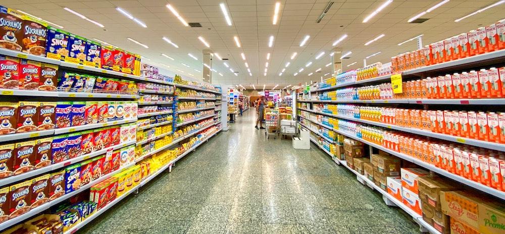 Foto de um corredor de supermercado com cereais de um lado e leite do outro.